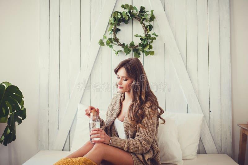 Glückliche junge Frau mit Flasche Wasser im Bett lizenzfreie stockfotografie