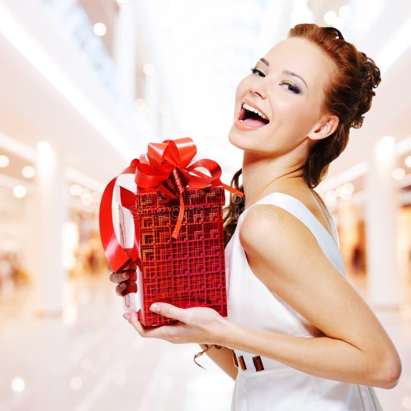 Glückliche junge Frau mit Geburtstagsgeschenk in den Händen lizenzfreies stockfoto