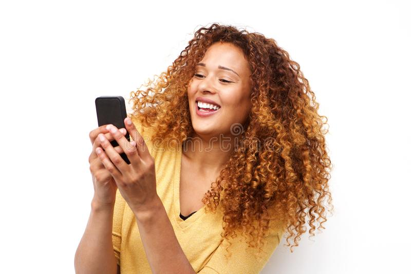 Glückliche junge Frau mit Holdingmobiltelefon des gelockten Haares durch weißen Hintergrund stockfoto