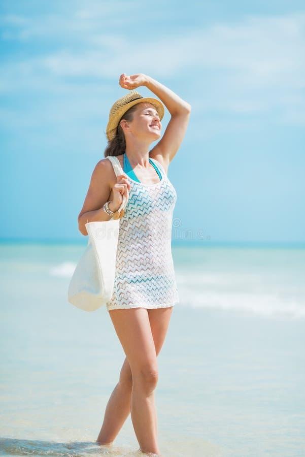 Glückliche junge Frau mit Hut und Tasche, die auf Seeküste gehen stockfoto