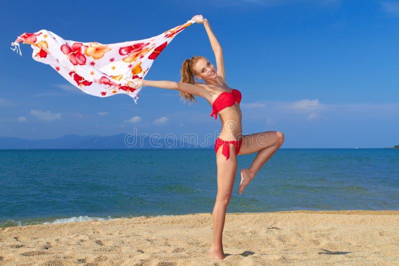 Glückliche junge Frau mit Schal auf tropischem Strand stockfotos