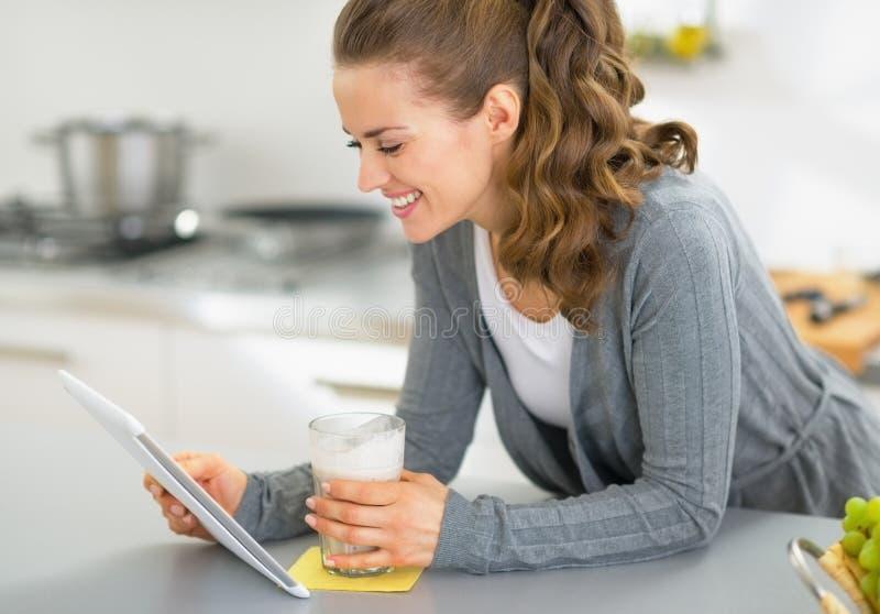 Glückliche junge Frau mit Smoothie unter Verwendung des Tabletten-PC in der Küche stockbilder
