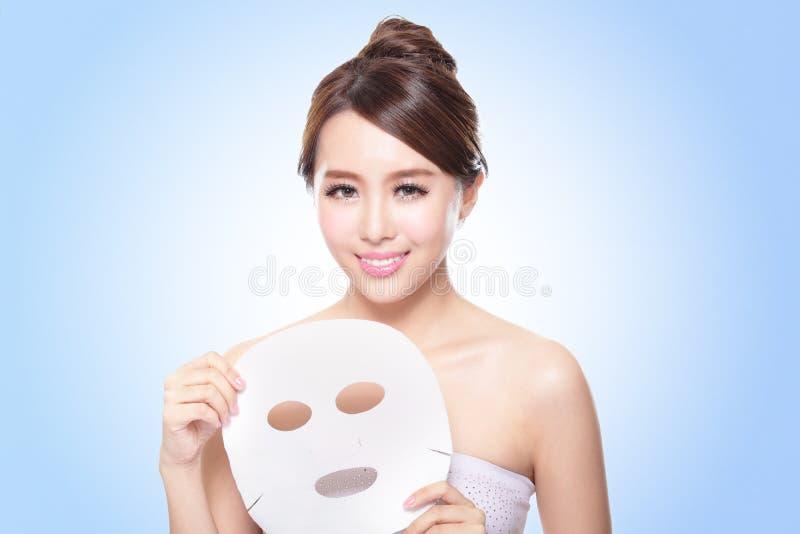 Glückliche junge Frau mit Stoffgesichtsbehandlungsmaske stockfotografie