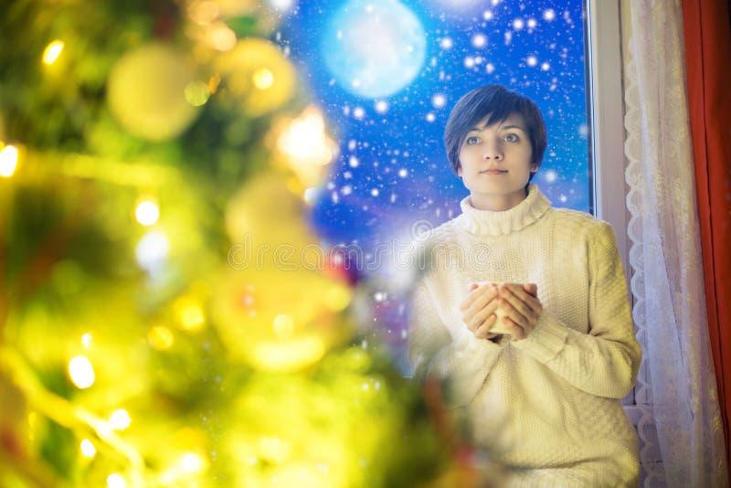 Glückliche junge Frau mit Tasse Kaffee oder Tee zu Hause über nächtlichem Himmel und Mond mit Schneefällen und Weihnachtsbaum stockbild