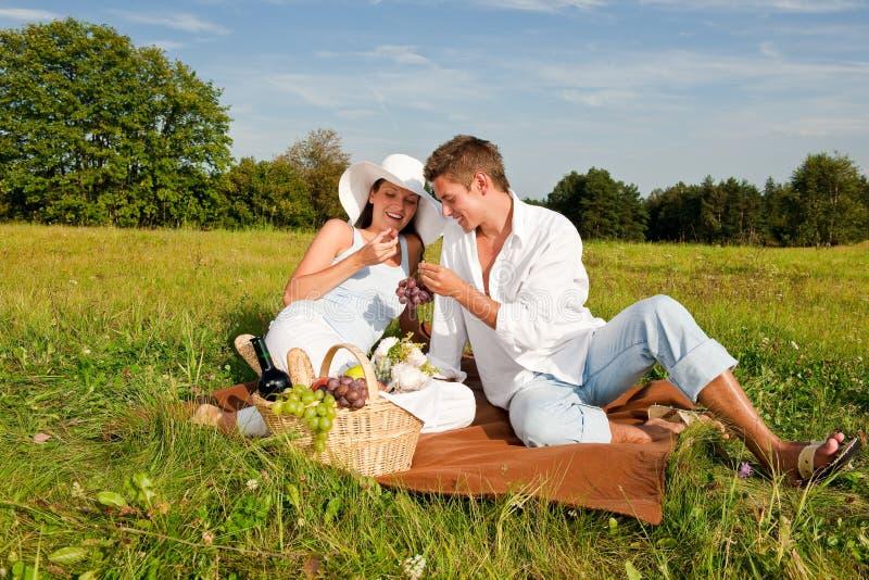 Glückliche junge Frau und Mann, die Picknick hat lizenzfreie stockfotos