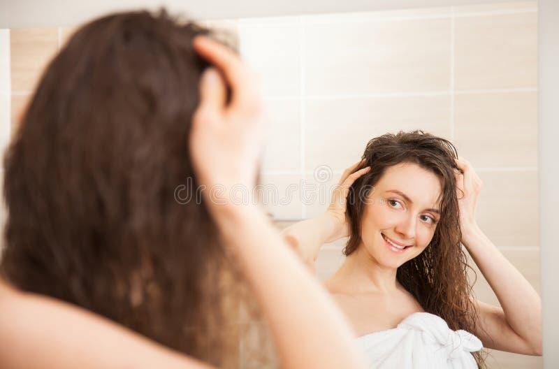 Glückliche junge Frau vor einem Spiegel stockbild