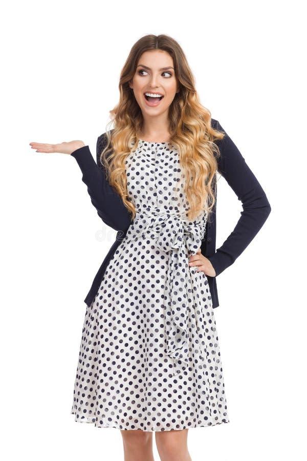 Glückliche junge Frau in Weiß punktiertem Kleid und in Wolljacke stellt sich dar lizenzfreie stockfotos
