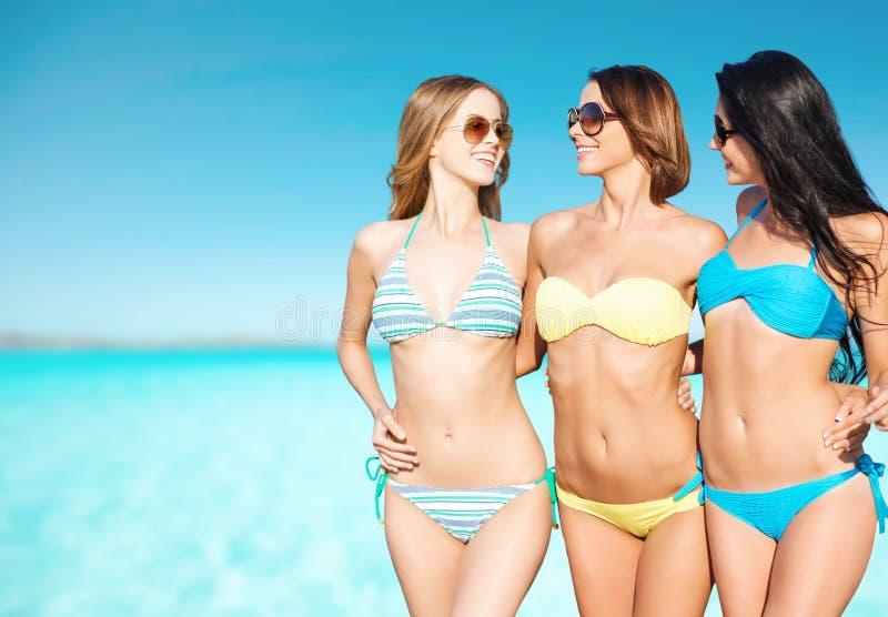 Glückliche junge Frauen in den Bikinis über blauem Himmel und Meer stockbilder