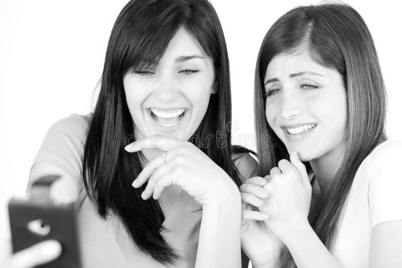 Glückliche junge Frauen, die Bilder nach selfie mit Smartphone schauend lachen lizenzfreie stockfotografie