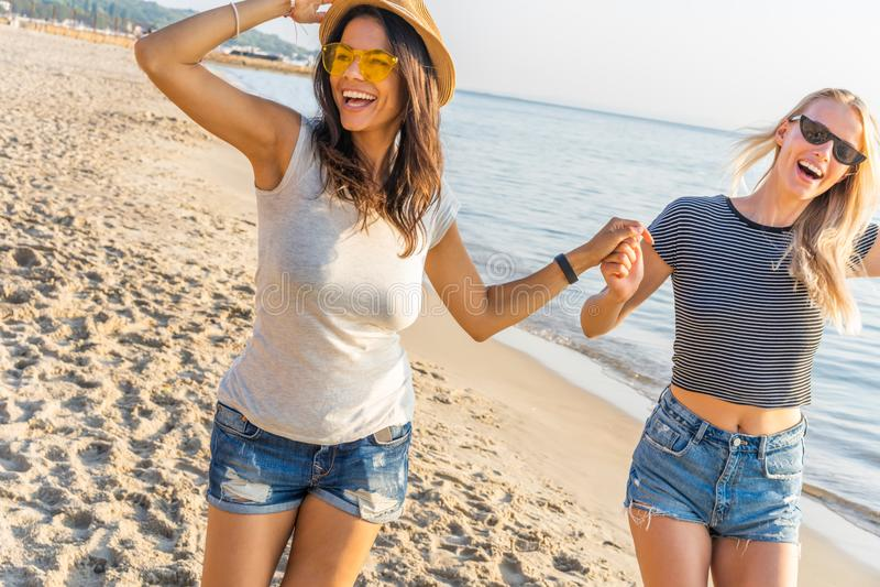 Glückliche junge Frauen, die entlang Küstenlinie an einem sonnigen Tag schlendern Zwei Freundinnen, die zusammen auf einen Strand stockfotografie