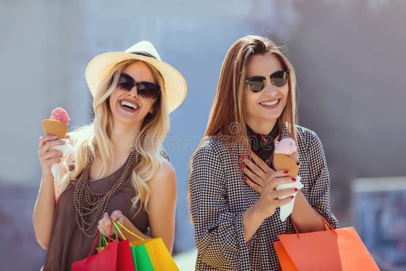 Glückliche junge Frauen mit den Einkaufstaschen und Eiscreme, die Spaß haben stockfoto