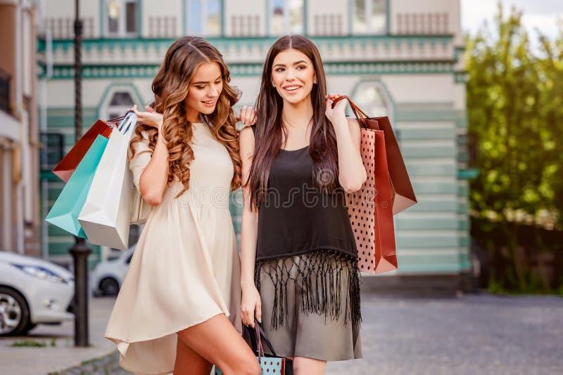 Glückliche junge Frauen mit Einkaufenbeuteln lizenzfreie stockfotos