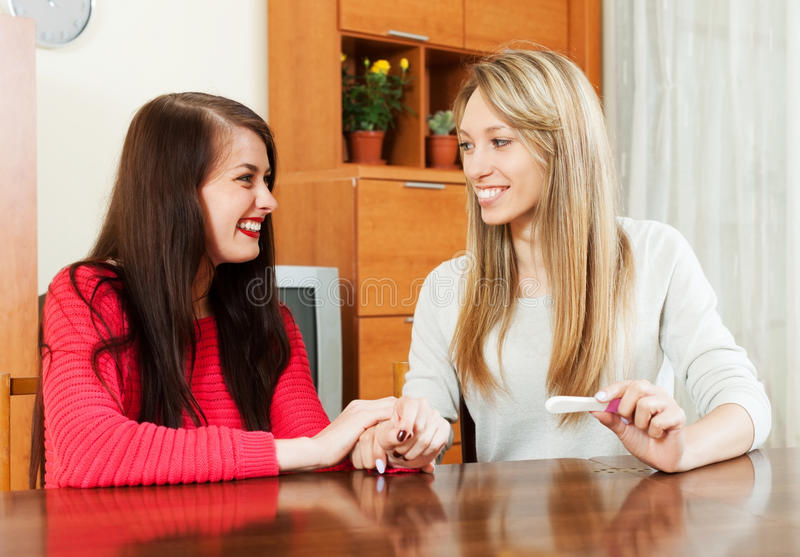 Glückliche junge Frauen mit Schwangerschaftstest stockfotos