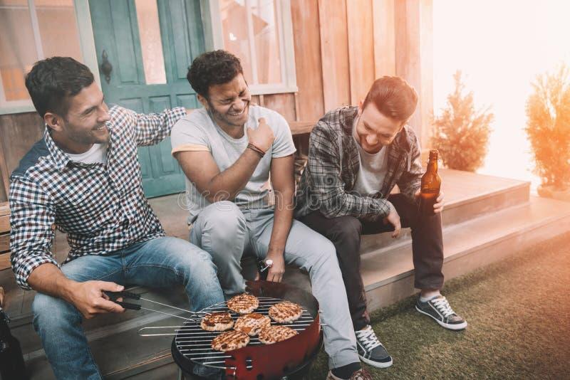 Glückliche junge Freunde, die Bier trinken und Spaß bei der Herstellung haben lizenzfreie stockbilder
