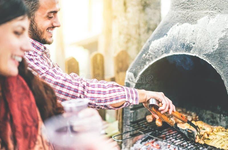 Glückliche junge Freunde, die eine Grillpartei grillt Fleisch im Hinterhof - gut aussehenden Mann kocht gegrilltes Rindfleisch fü stockfoto