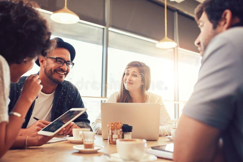 Glückliche junge Freunde, die an einem Café sitzen und sprechen stockfotografie
