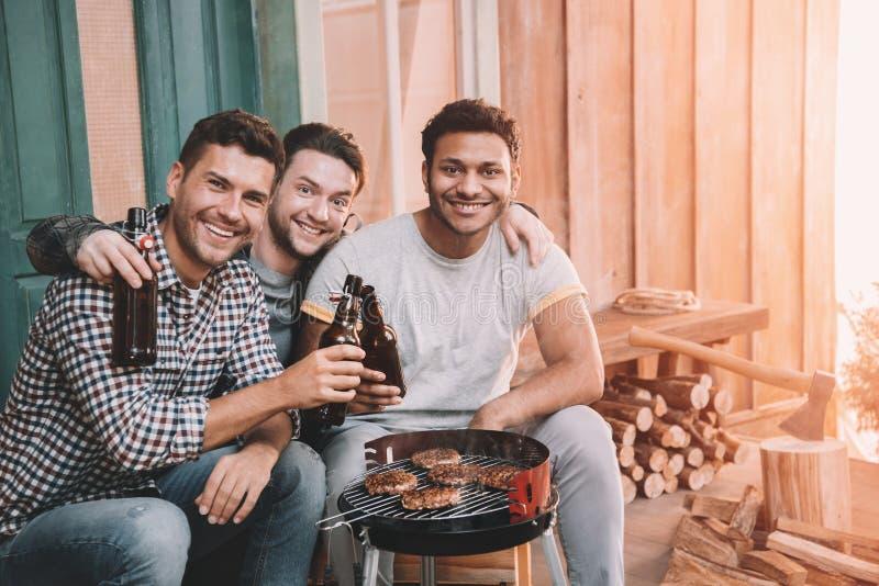 glückliche junge Freunde, die Grill machen und Bier auf Portal trinken stockfoto