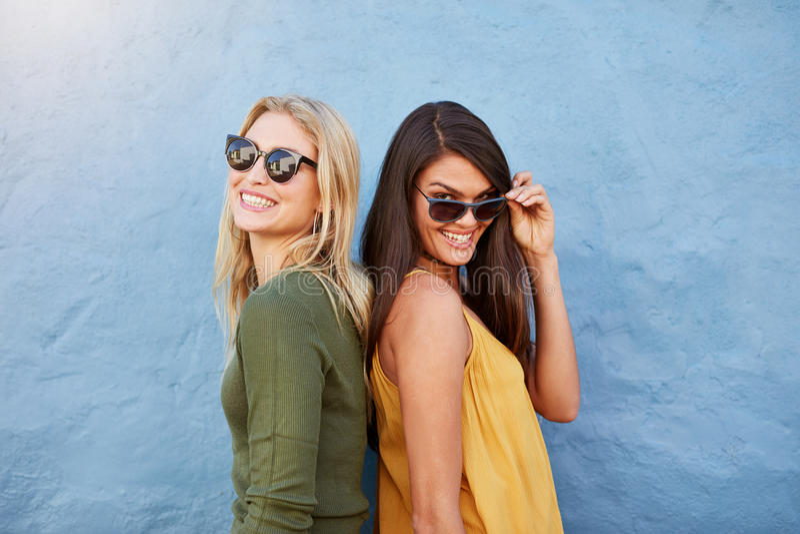 Glückliche junge Freundinnen, die zusammen stehen lizenzfreies stockbild