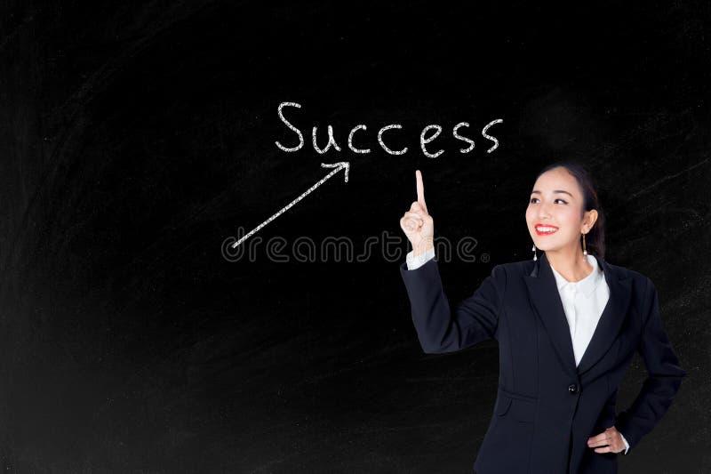 Glückliche junge Geschäftsfrau, die auf Erfolgstext mit Tafel zeigt lizenzfreie stockfotos