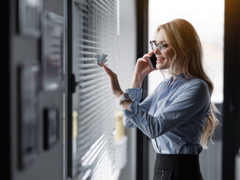 Glückliche junge Geschäftsfrau, die am Handy spricht lizenzfreie stockfotos