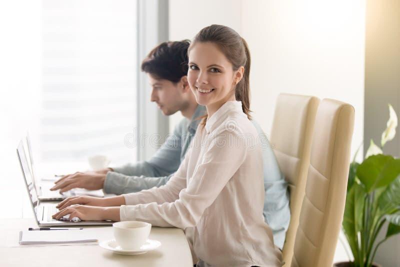 Glückliche junge Geschäftsfrau, welche die Kamera, arbeitend mit Mann c betrachtet stockfoto