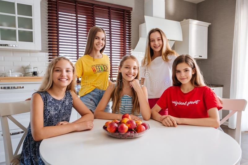Glückliche junge Gruppe Freundjugendlichen, die in der Küche sitzen stockbilder