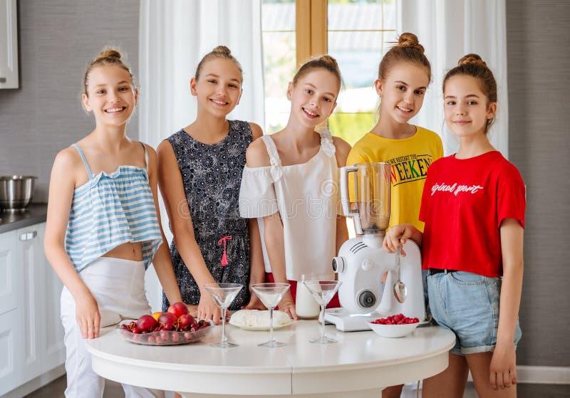 Glückliche junge Gruppe Freundjugendlichen, die eine Frucht Smoothies in der Küche machen stockfotos