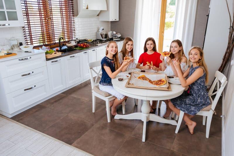 Glückliche junge Gruppe Freundjugendlichen, die eine Pizza in der Küche essen lizenzfreies stockfoto