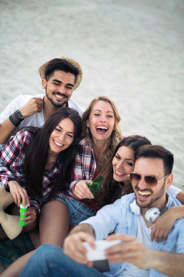 Glückliche junge Gruppe von Personen, die selfies auf Strand nimmt lizenzfreie stockfotos