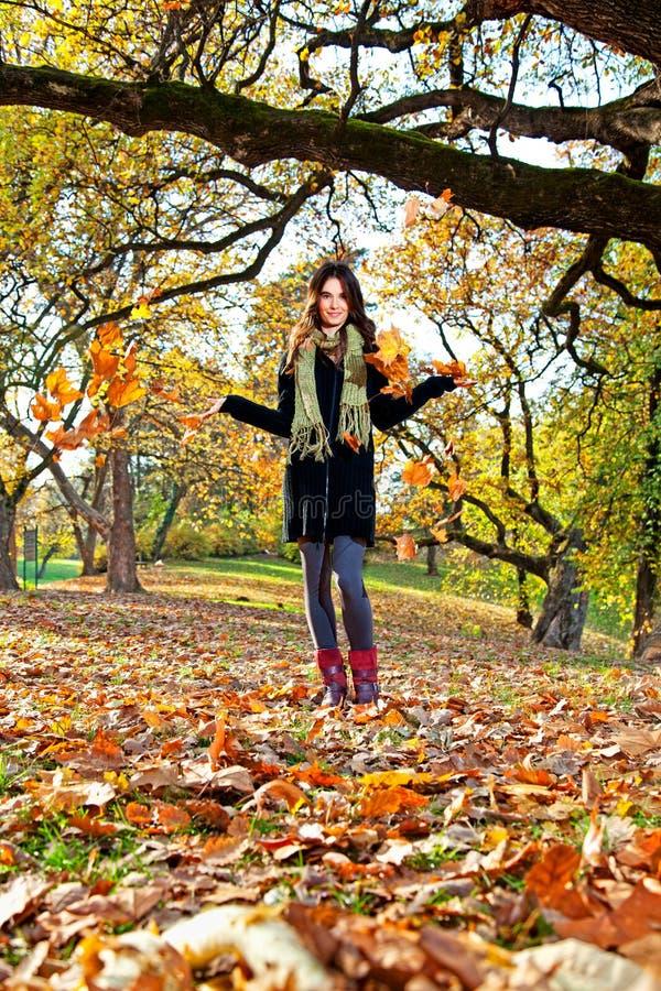 Glückliche junge hübsche Frau am Herbstpark. lizenzfreie stockfotografie