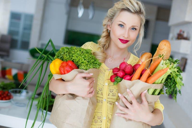 Glückliche junge Hausfrau mit den Taschen voll vom Gemüse stockfotografie