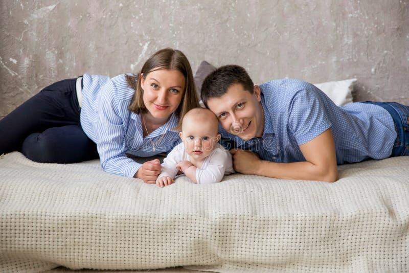 Glückliche junge kaukasische Familie, die auf Bett liegt stockbilder