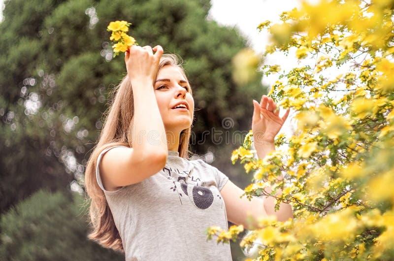 Glückliche junge kaukasische Frau, die Blumen genießt, im Frühjahr zu blühen lizenzfreies stockbild