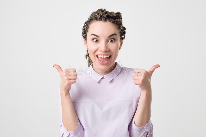 Glückliche junge kaukasische Frau, die Daumen oben auf weißem Hintergrund gibt lizenzfreie stockfotos