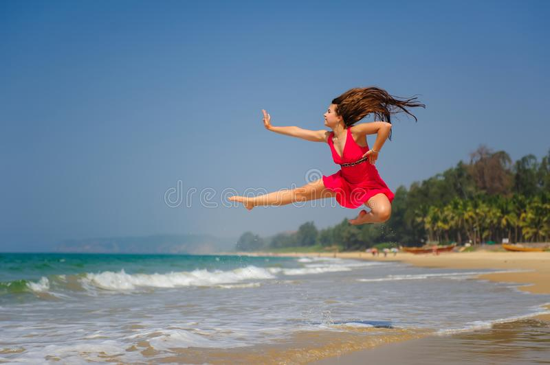 Glückliche junge kaukasische Frau, die hoch über nass Sand im tropischen Meer am sonnigen Tag springt Barfuß ein sportliches Mädc stockfotografie