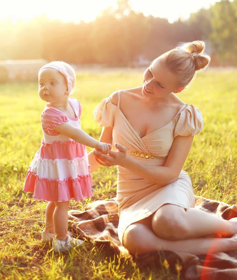 Glückliche junge kleine Tochter der Mutter und des Babys, die ein Kleid trägt stockbild