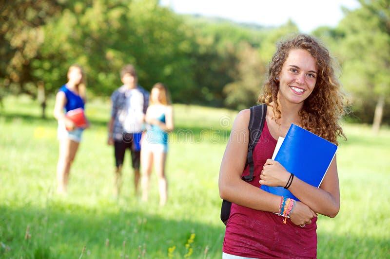 Glückliche junge Kursteilnehmer des Portraits im Park lizenzfreie stockbilder