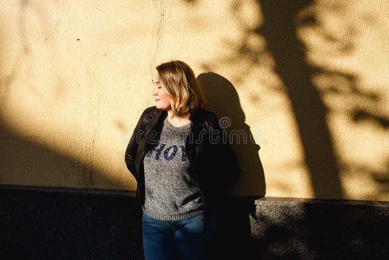 Glückliche junge, kurvige Frau, die nahe gelbe Mauer steht Girl bei schönem sonnigem Wetter Sie trägt blaue Jeans und lizenzfreie stockbilder