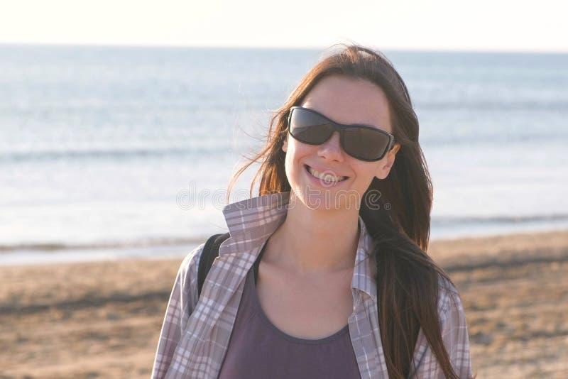 Glückliche junge lächelnde brunette Frau in der Sonnenbrille am Sandstrand durch das Meer stockfoto