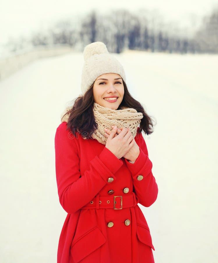 Glückliche junge lächelnde Frau, die einen roten Mantel, eine Strickmütze und einen Schal im Winter trägt stockfotografie