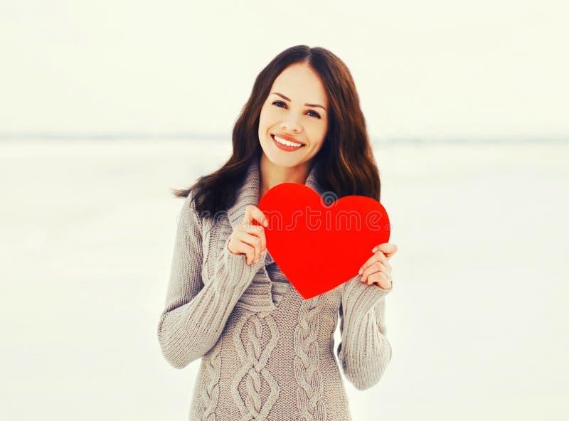 Glückliche junge lächelnde Frau mit großem rotem Papierherzen im Winter stockfoto