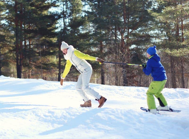 Glückliche junge lächelnde Mutter des Winters mit Sohnkind gehen Ski zu fahren, Spaß im Wald auf Berg habend stockbilder