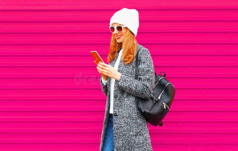 Glückliche junge lächelnde Studentin mit tragender Manteljacke des Telefons, Hut, Rucksack gehend auf Stadtstraße, stockbilder