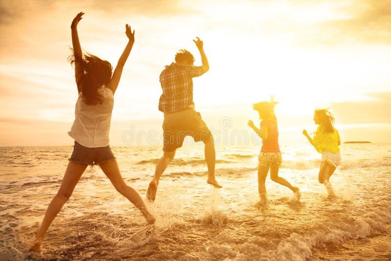 glückliche junge Leute, die auf den Strand tanzen lizenzfreies stockbild