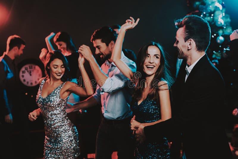 Glückliche junge Leute, die auf neues Jahr-Partei tanzen stockfotografie