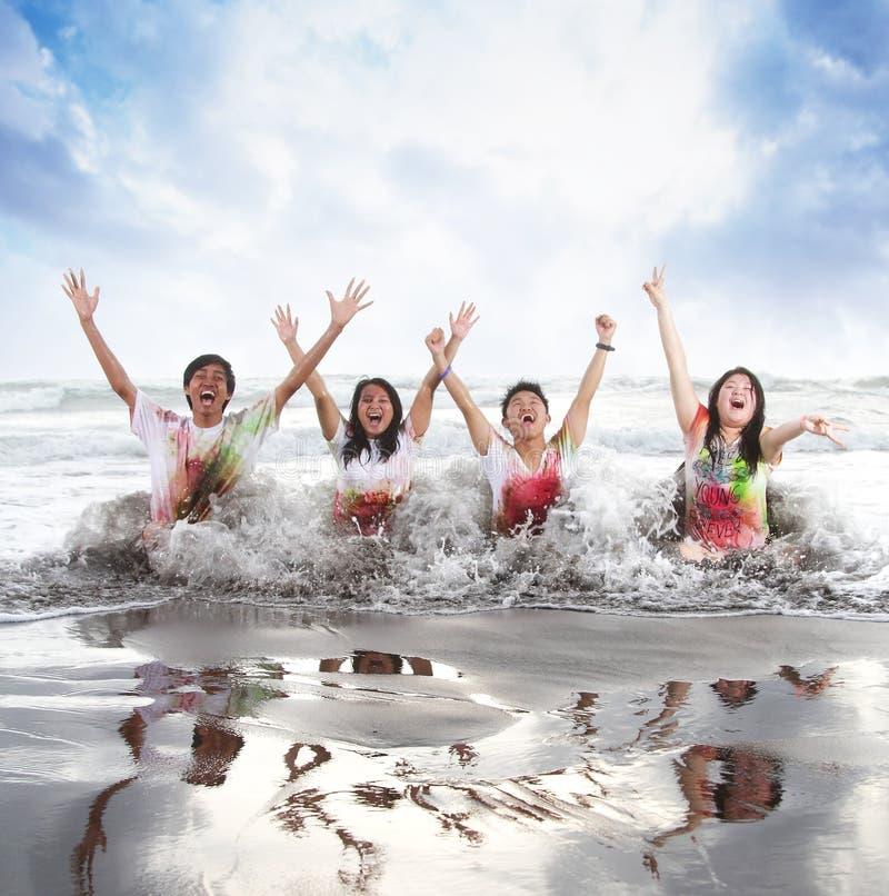 Glückliche junge Leute, die einen Strand im Sommer mit Zeitlupe und undeutlichem Konzept genießen stockbild