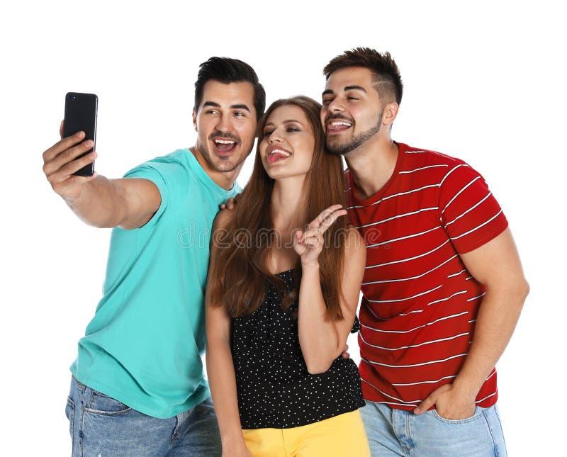 Glückliche junge Leute, die selfie auf Weiß nehmen stockbilder