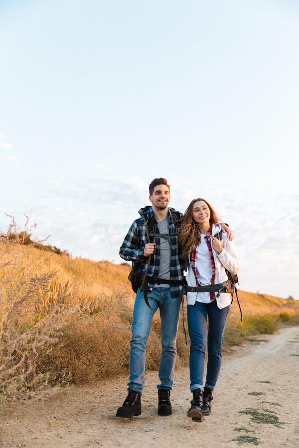 Glückliche junge liebevolle Paaraußenseite mit Rucksack im freien alternativen Ferienkampieren stockfotografie