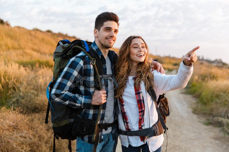 Glückliche junge liebevolle Paaraußenseite mit Rucksack im freien alternativen Ferienkampieren lizenzfreie stockbilder