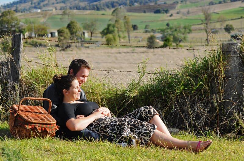 Glückliche junge Liebhaber, die draußen lachen u. lächeln lizenzfreie stockbilder